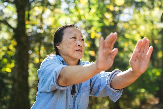 Mature asian woman practicing tai chi outside.