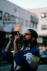 a man with a beard takes pictures in the streets of san francisco