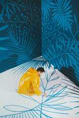 Street artist in yellow raincoat drawing blue plants