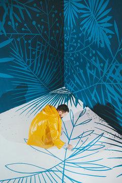 Street artist in yellow raincoat drawing blue plants
