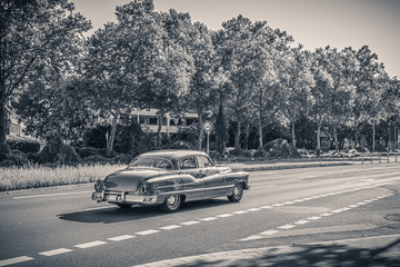 Black and white monochrome photo of an american oldtimer car from the 1950s. Vintage USA car on the...