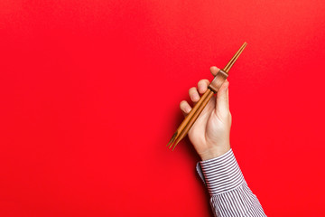 Cropped image of male hand holding chopsticks on red background. Asian food concept with copy space
