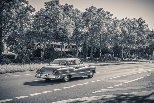 Black and white monochrome photo of an american oldtimer car from the 1950s. Vintage USA car on the street on a sunny summer day. Retro travel, traffic concept.