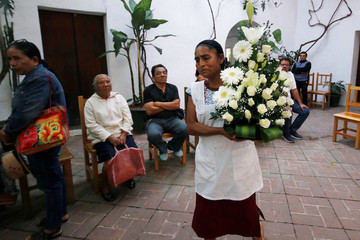 A woman carrying a flower bouquet arrives to the memorial for late Mexican graphic artist Francisco Toledo at the Graphic Arts Institute of Oaxaca (IAGO) in Oaxaca