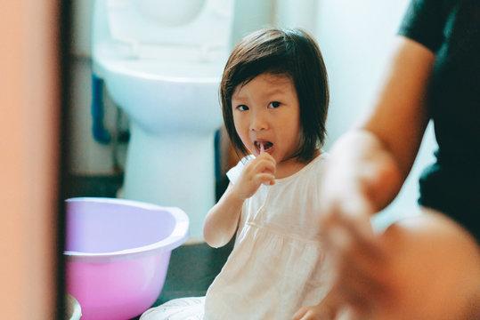little girl brush her teeth