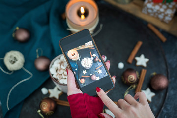 Woman's hand taking picture of cup of Hot Chocolate with marshmallows with smartphone