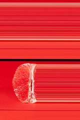 Peeled half of ripe grapefruit fruit on red background with copy space. Organic food. Modern design with one pixel strips width