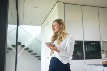 Businesswoman holding tablet in modern home