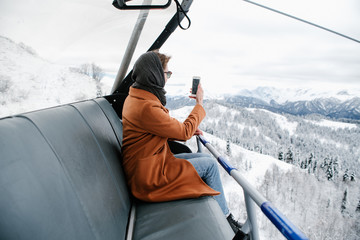 Woman taking photo of mountains from chairlift