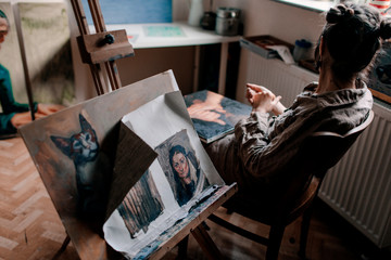 Female artist sitting in her studio with paintings