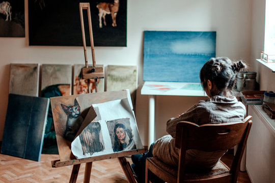 Rear view of female artist sitting in her studio in front of painting
