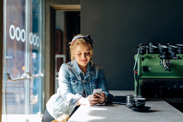 Young woman in coffee shop, using smartphone, taking pictures