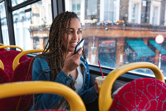 Portrait of smiling young woman on the phone sitting in bus looking out of window, London, UK