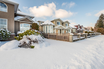 A perfect neighbourhood. Houses in suburb at Winter in the north America. Luxury houses covered...