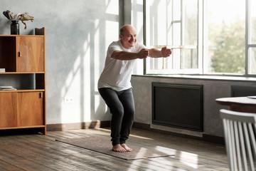 Senior hispanic man practicing yoga indoors at living room doing Chair pose or Utkatasana