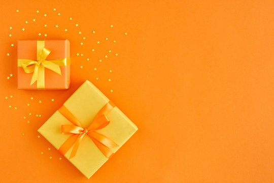 Two gift boxes with ribbon and bow on orange background with gold stars . Top view and space for text.