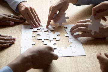 Diverse people assemble jigsaw puzzle searching right decision
