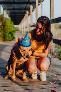Casual young woman resting next to brown dog with party hat