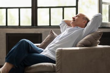 Photo sur Aluminium Detente Happy senior hispanic man relaxing on sofa at home