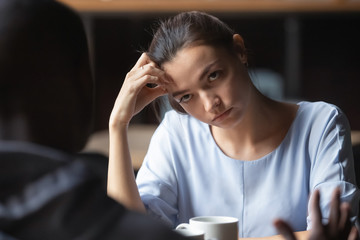 Bored unhappy girlfriend listening to African American boyfriend in cafe