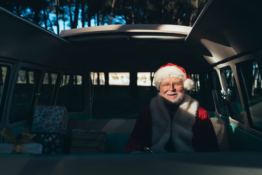 Man dressed as Santa Claus sitting in van with gifts