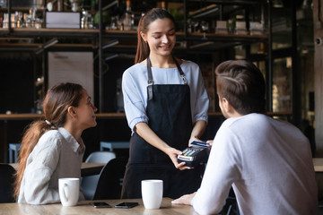 Customer paying by contactless credit card, attractive waitress holding reader