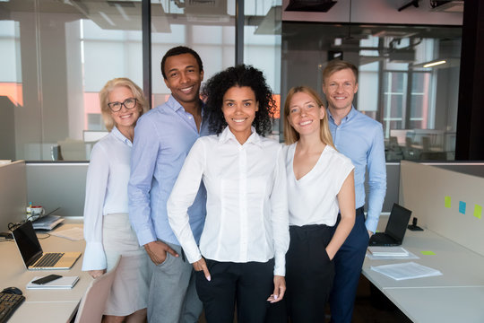 Portrait of smiling diverse employee look at camera making picture
