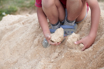 little boy playing with sand on the beach stock photo