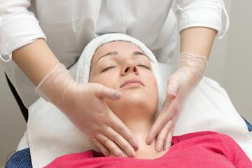 Fototapeta Face skin care. Beautician applying beauty oil mask on face using brush In spa salon