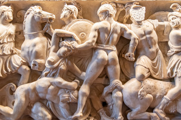Old sculptures carved on marble wall showing ancient soldiers attacking women