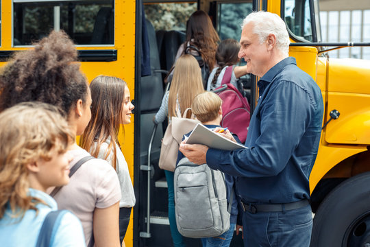 Classmates going into school bus while driver checking attendance smiling happy close-up