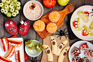 Healthy Halloween fruit snacks. Selection of fun, spooky treats. Top view table scene over a rustic...