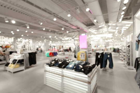 Sale and seasonal change of collection. Blurred View of fashionable clothing store in shopping center. Led lighting on the ceiling. Fire system and air conditioning system in retail shop.