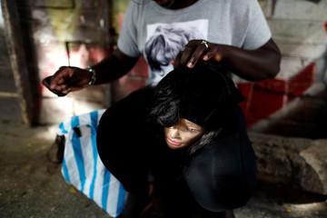 A woman prepares her wig in the Medina neighbourhood in Dakar
