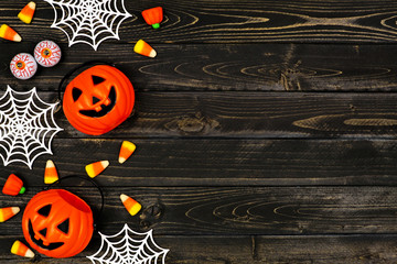 Halloween side border of scattered candy and decor. Flat lay over a black wood background with copy space.