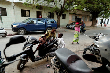 A boy who works at a motorcycle repair shop takes a rest in Medina neighbourhood, in Dakar