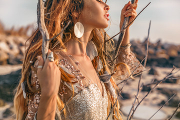 close up portrait of beautiful young woman model with boho accessories outdoors at sunset