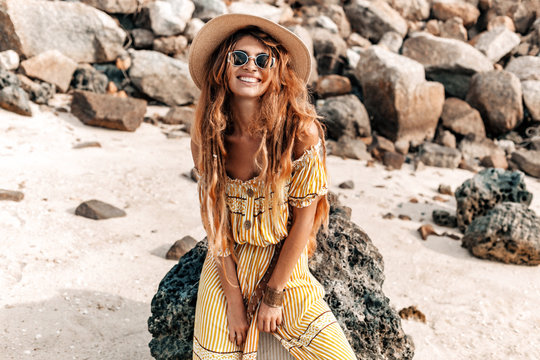beautiful young stylish boho woman in elegant dress outdoors wearing hat and sunglasses at sunset