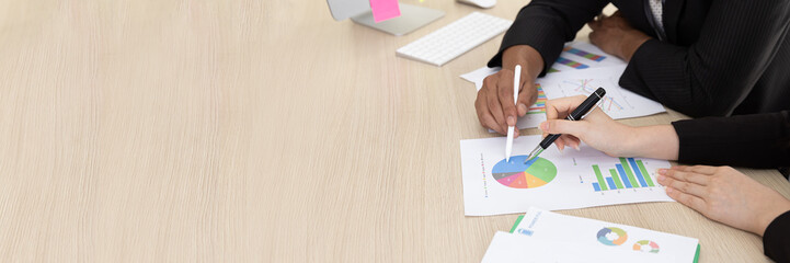 Close up Hand of businessman in black suit talking  planning business strategy. They pointing paperwork Marketing plan researching. Business teamwork, brainstorming concept. with copy space