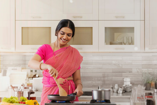woman in saree cooking in the kitchen