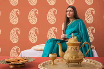 woman in saree having tea at home