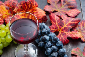 glass of red wine and grapes on black wooden table background Fototapete