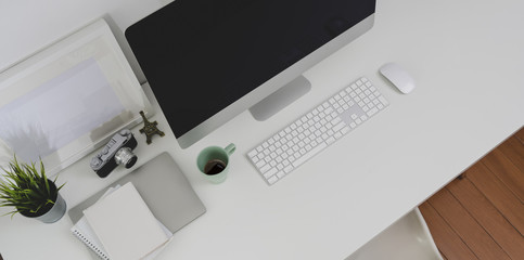 Top view of desktop computer and office supplies with copy space in minimal office room