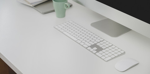 Cropped shot of desktop computer and office supplies with copy space in minimal office room