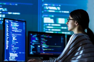 Software developer freelancer woman female in glasses work with program code C++ Java Javascript on wide displays at night Develops new web desktop mobile application or framework Projector background Fototapete