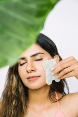 Beautiful Indian woman using gua sha stone to massage her face - vertical with leaf and copy space - green beauty concept