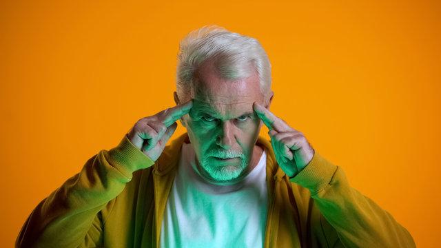 Elderly male mentalist demonstrating mind-reading power at camera, telepathy