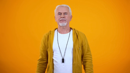 Experienced aged sport coach looking at camera on orange background, profession Wall mural
