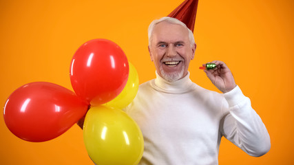 Positive elderly male with balloons and party blower looking at camera, fun