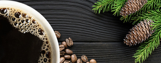Foto op Plexiglas Cafe Coffee cup with coffee beans and christmas tree branch on black wooden background